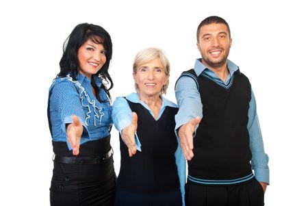manos estrechadas: Tres personas de negocios de pie con sus manos directamente para el apret�n de manos y sonriendo aislados sobre fondo blanco