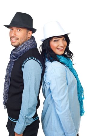 Happy young couple with white and black hat and scarves standing back to back and smiling to you isolated on white background photo