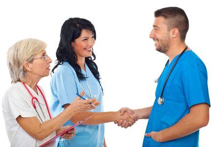 manos estrechadas: Tres médicos éxito dan apretón de manos en la reunión y la mujer senior make conoció o la presentación de la joven al hombre