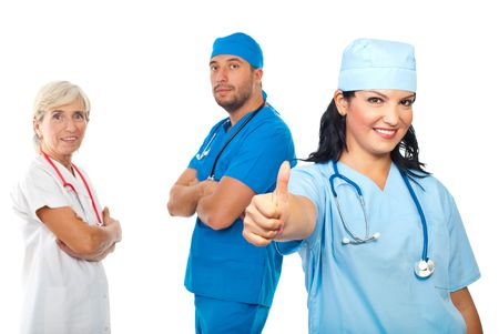 Successful group of three doctors standing with hands crossed and a young doctors woman giving thumb up in front of camera isolated on white background Stock Photo - 7837264