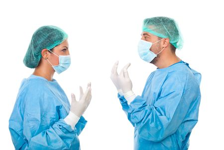Two doctors in  sterile uniforms standing face to face, holding up their hands in protective gloves   and having a conversation before operation isolated on white background photo