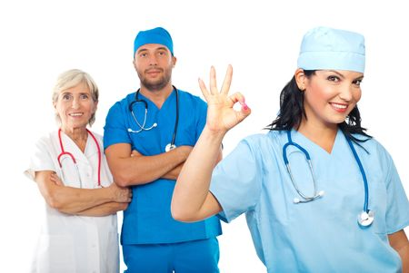 Doctor woman showing okay sign while her team  standing with hands crossed in background photo