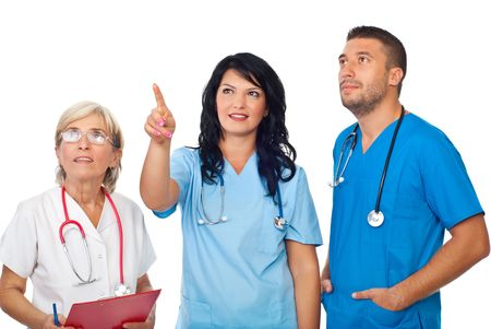 Friendly young doctor woman pointing up to copy space and all team looking there isolated on white background photo