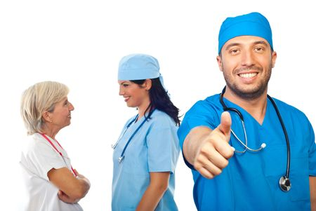 Smiling doctor male giving thumb up in front of image while his team having conversation and laughing in background Stock Photo - 7837531