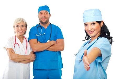 manos estrechadas: Mujer de médico alegre dar apretón de manos o gesto de bienvenida de signo y su equipo sonriendo en segundo plano aislado en blanco  Foto de archivo