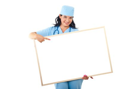 Smiling doctor woman holding a blank banner and pointing to copy space isolated on white background photo