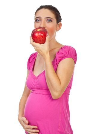 Pregnant eating red big apple and holding her tummy isolated on white background photo