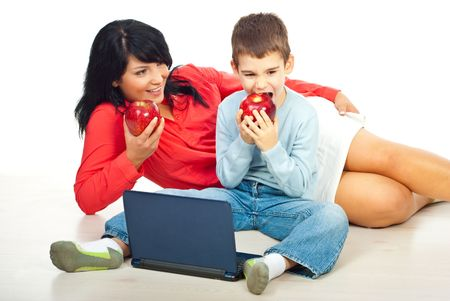 Mother and son eating big red  apples  ,sitting on floor and having conversation photo
