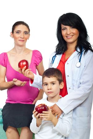 Friendly doctor woman giving red apples to a pregnant and her little son isolated on white background photo