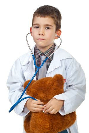 Future doctor boy examine his teddy bear with stethoscope isolated on white background photo