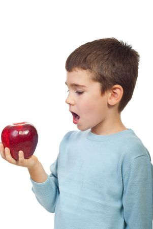 Small boy preparing to bite a big red apple and standing in semi profile isolated on white background photo