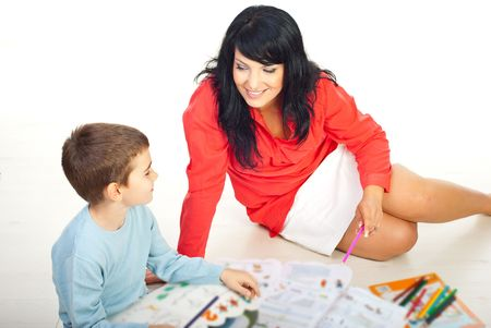 teaching adult: Smiling mother and her son having conversation and sitting on floor with books and colorful pencils around them  Stock Photo