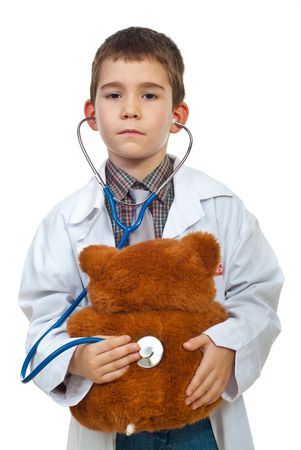 Little boy doctor examine teddy bear isolated on white background photo