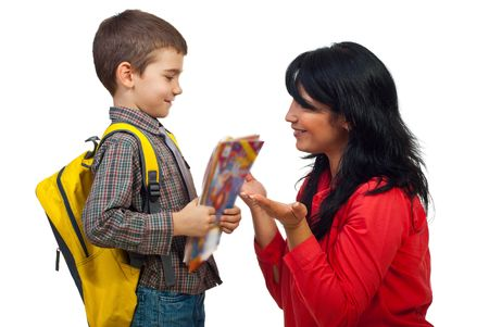 Mom giving explanation to her little son and preparing him for fist day of school,the boy holding bag and  books and looking attentive to his mother