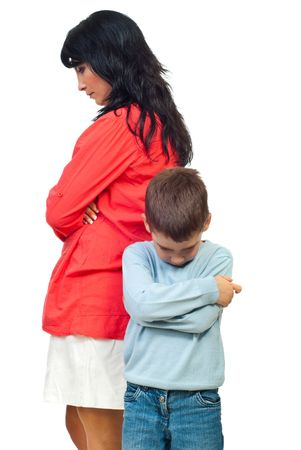 Sad mother and son standing with hands crossed and looking down after conflict isolated on white background photo