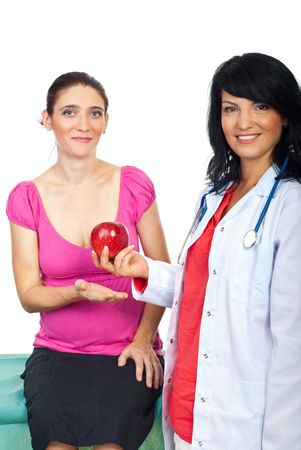Smiling healthcare doctor giving a red apple to a pregnant patient woman  photo