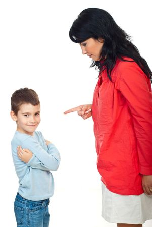 punish: Mother arguing her child .The boy smile and  standing with hands crossed and does not pay attention to her