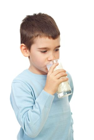 Child boy standing in semi profile and drinking a glass of milk isolated on white background photo
