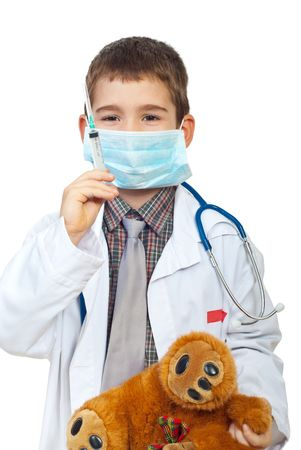 doctor toys: Future doctor boy with protective mask preparing to inject his teddy bear isolated on white background