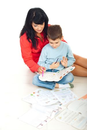 Mother helping her son with homework and making math exercises on floor in their home
