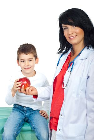 Happy doctor woman giving a red apple to a smiling child with missing teeth  photo