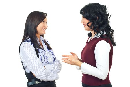 converse: Two smiling women standing face to face and  having happy conversation while one of them giving explanation and gesticulate with hands isolated on white background
