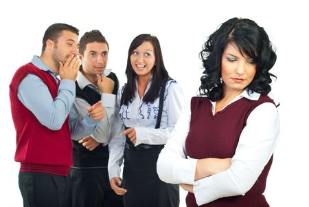gossip: Drie mensen roddel en grap op achtergrond over hun collega-vrouw en ze staan met handen gekruist en naar beneden te kijken met een triest gezicht  Stockfoto