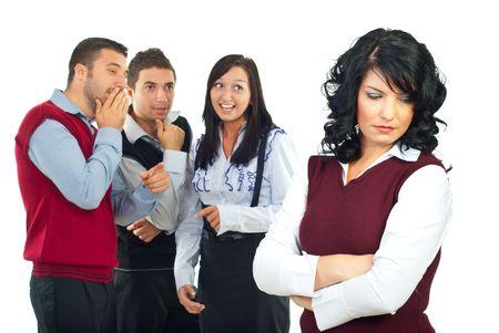 Tres personas chismes y broma en segundo plano sobre la mujer de su colega y ella permanente con las manos cruzadas y mirando hacia abajo con una cara triste