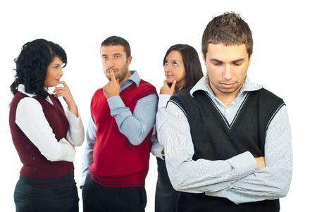 gossip: Mensen uit het bedrijfsleven groep met problemen denken op oplossingen terwijl een jonge man die voor camera met handen gekruist en verdrietig gezicht Stockfoto