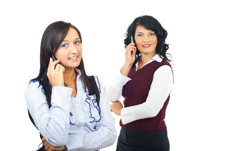 Two women talking by cell phones and smiling isolated on white background photo