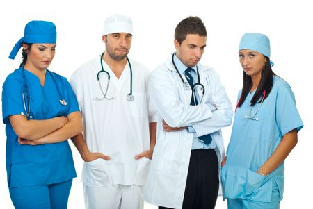 hospital stress: Disappointed team of different doctors standing in a row and looking down or at camera isolated on white background