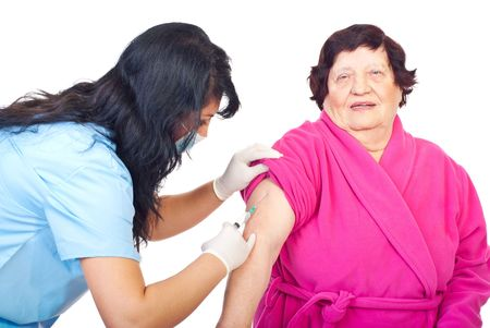 Nurse woman with protective mask and gloves vaccine her elderly woman patient photo