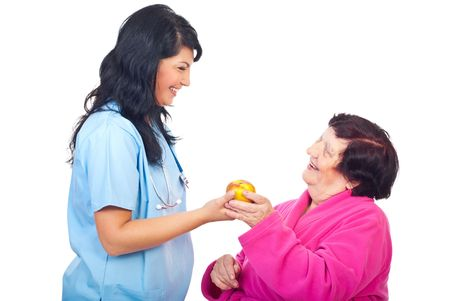 Happy doctor woman offering an apple to a elderly patient and both laughing isolated on white background photo