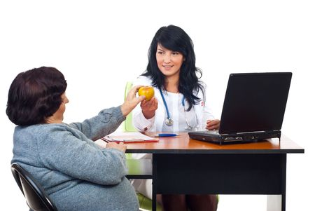 Physican woman offering apple to elderly female  in her cabinet isolated on white background Stock Photo - 7985614