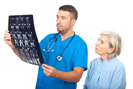 Serious doctor man showing results of magnetic resonance imaginig to a senior patient and both being worried isolated on white background photo