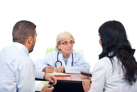 Senior doctor woman offering medical adivices to a young couple  in office photo