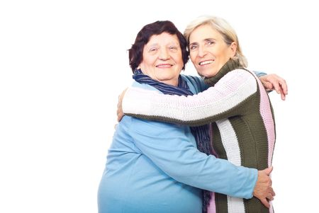 octogenarian: Portrait of happy elderly mother embracing senior daughter  over white background,copy space for text message in left part of image