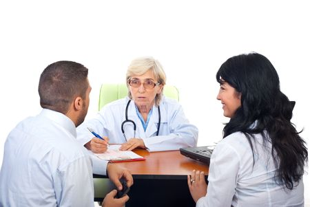 Senior doctor woman having conversation with young couple in office photo