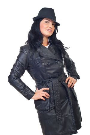 Beautiful detective woman in  long leather jacket and black hat isolated on white background photo