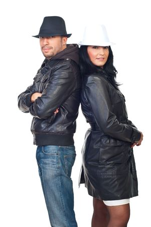 Fashionable young couple in leather jackets and hats standing back to back isolated on white background photo