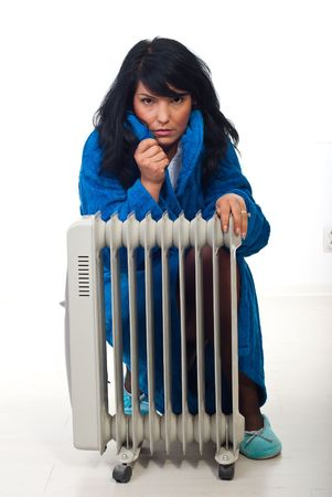 Woman shivering and sitting near radiator trying to heat up  Stock Photo