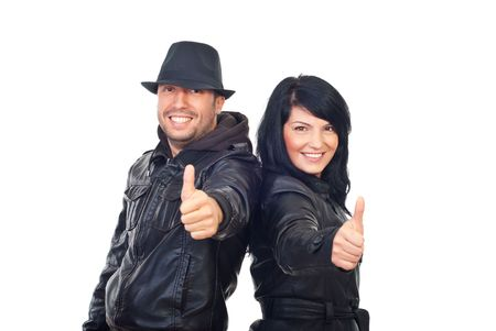 Successful couple in leather jackets giving thumbs up and smiling isolated on white background photo