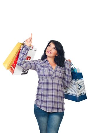 Smiling woman holding shopping bags and pointing up to copy space showing big promotion or discount isolated on white background photo