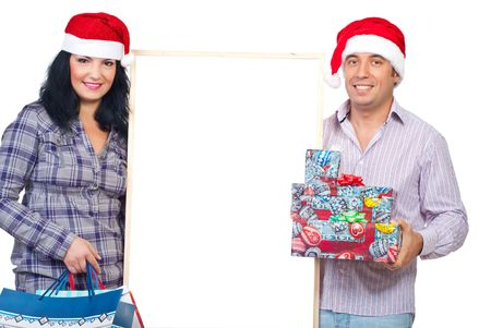 Cheerful couple holding blank banner and Christmas gifts isolated on white background photo