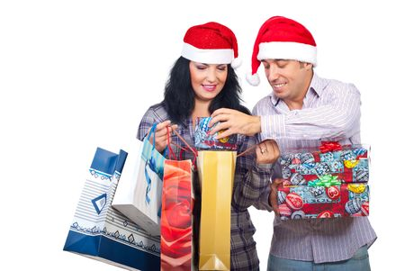 Laughing couple with Santa hats brought Christmas presents  and the man trying to introduce a small gift box in a shopping   bag isolated on white background photo