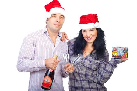 Happy Christmas couple in Santa hats holding a gift,champagne and glasses isolated on white background photo