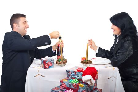 Happy husband opening champagne bottle and preparing for toast with his wife at Christmas table  photo
