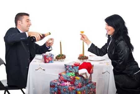 Happy Ccouple sitting at Christmas table and man pouring champagne in glasses for toasting with his wife  Stock Photo - 8042164