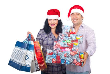 Smiling couple with santa hats holding shopping bags and Chriostmas presents isolated on white background photo