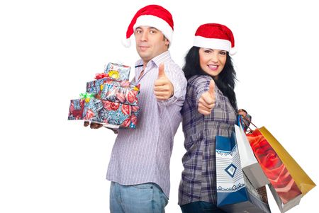 Successful happy couple with Santa hats holding presents and giving thumbs up isolated on white background photo